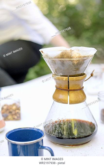 Close up of a glass coffee maker on a table in a garden