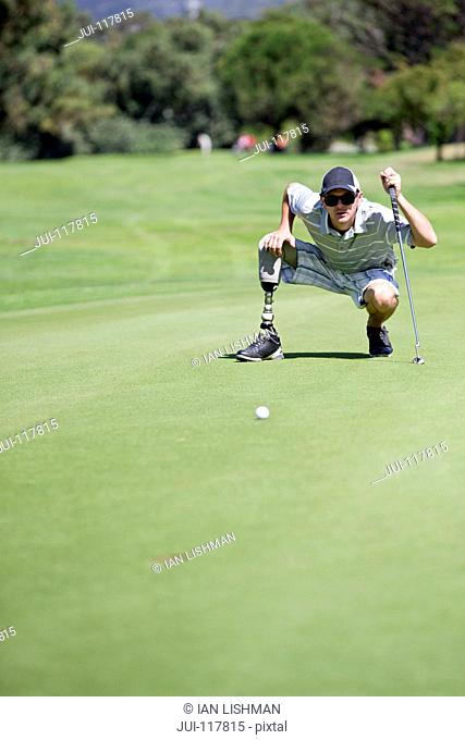 Male Golfer With Artificial Leg On Course Lining Up Ball On Green