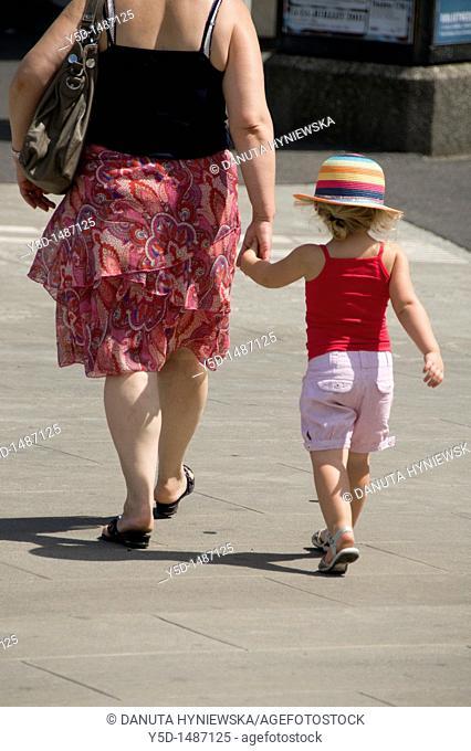 mother with little girl walking the street, hand in hand, Geneva, Switzerland
