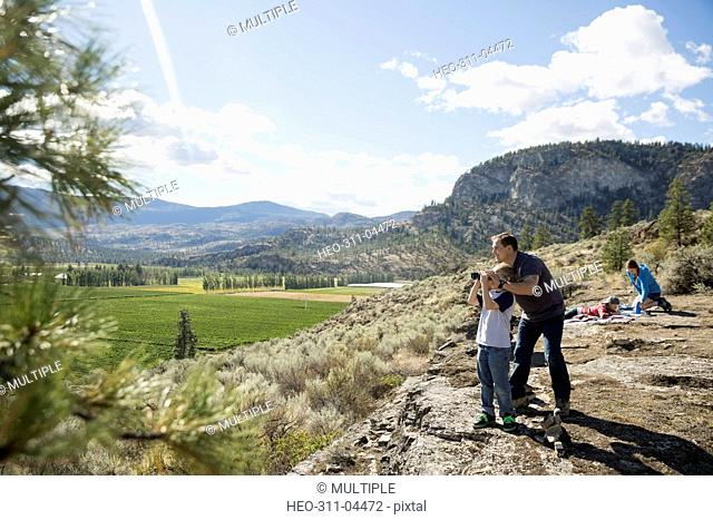 Father and son with binoculars looking at sunny rural vineyard view