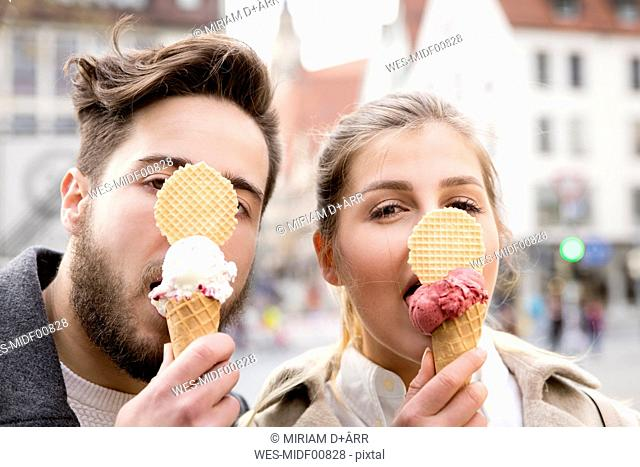 Funny portrait of young couple eating ice cream