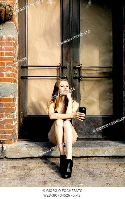 Young woman sitting in the street on a doorstep, holding a cup of coffee