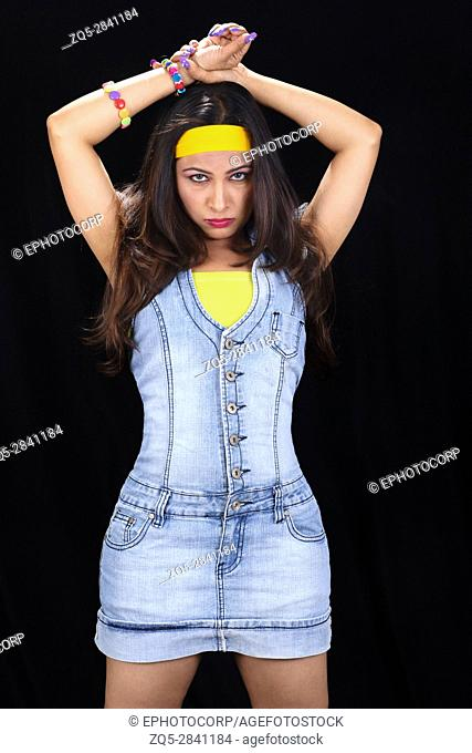 Portrait of young woman in denim with hands over head