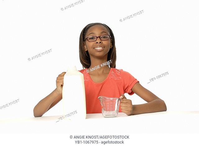 10 year old girl measuring milk in measuring cup