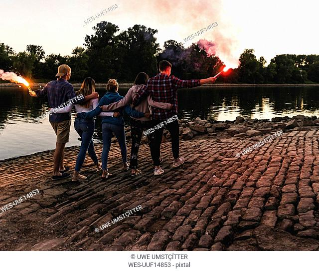 Group of friends walking at the riverside in the evening with torches