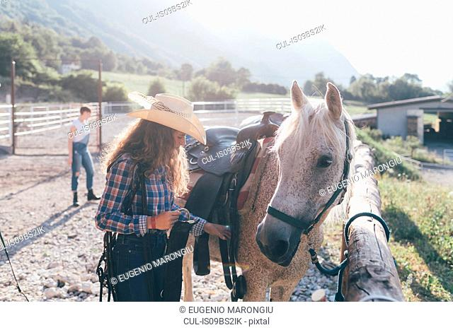 Young cowgirl checking saddle in rural equestrian arena
