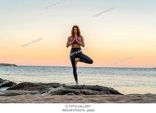 Young woman practicing yoga on the beach, doing tree pose, during sunset in calm beach, Costa Brava, Spain