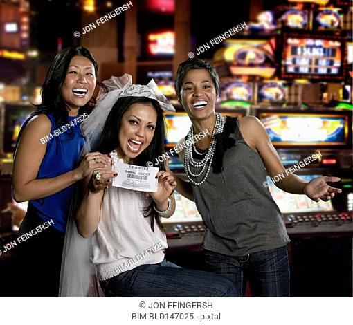 Excited women holding gaming voucher in casino