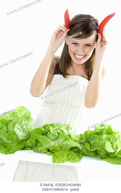 young woman with lettuce and chilli pepper