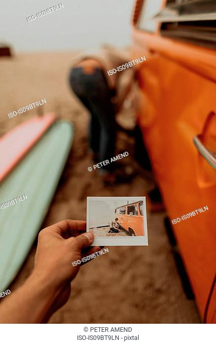 Young woman holding instant photo of boyfriend removing flat tyre on recreational vehicle at beach, Jalama, California, USA
