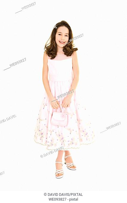 Young caucasian girl dressed in a Easter dress and standing on a white background