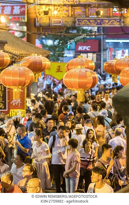Beijing, China - Crowds of people walking through the Donghuamen Snack Night Market, a large outdoor market that is an attraction for locals and tourists