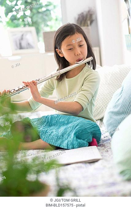 Chinese girl practicing flute on bed