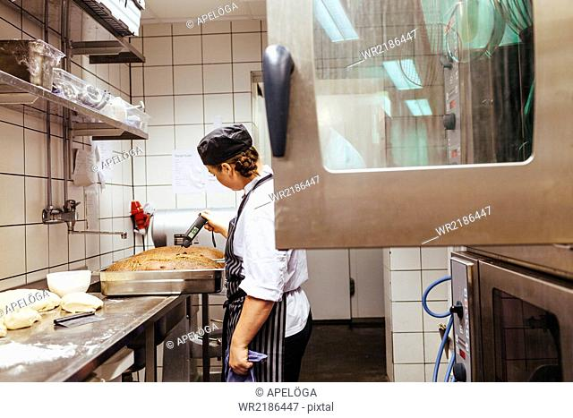 Chef checking temperature of bread in commercial kitchen