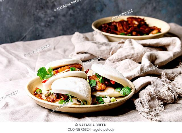 Asian sandwich steamed gua bao buns with pork belly, greens and vegetables served in ceramic plate on table with linen tablecloth