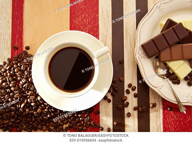 Coffee cup breakfast with chocolate and coffee beans on red brown wooden table