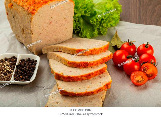 Meat product in the form of bread with spices and on baking paper