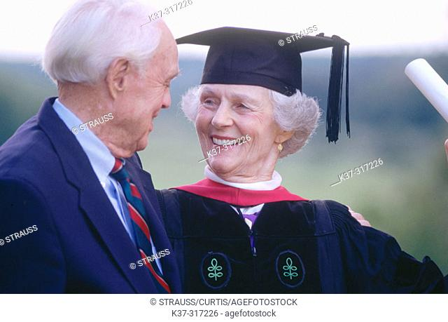 Senior woman wearing graduation cap and gown being congratulated by her husband on receiving degree