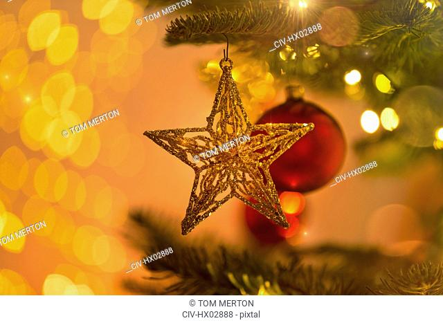 Close up gold star ornament hanging from Christmas tree branch