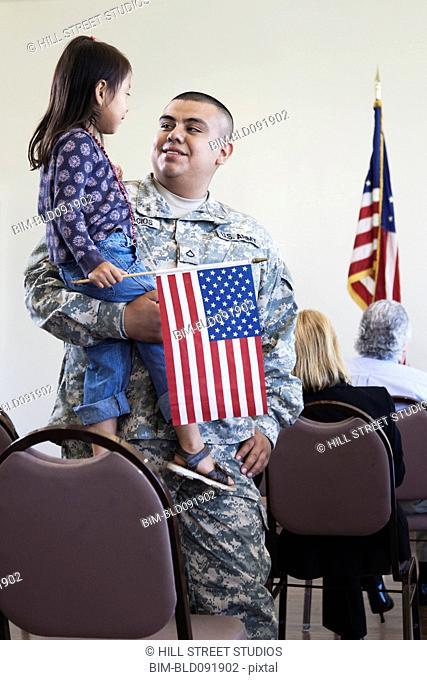 Hispanic soldier holding daughter at political gathering