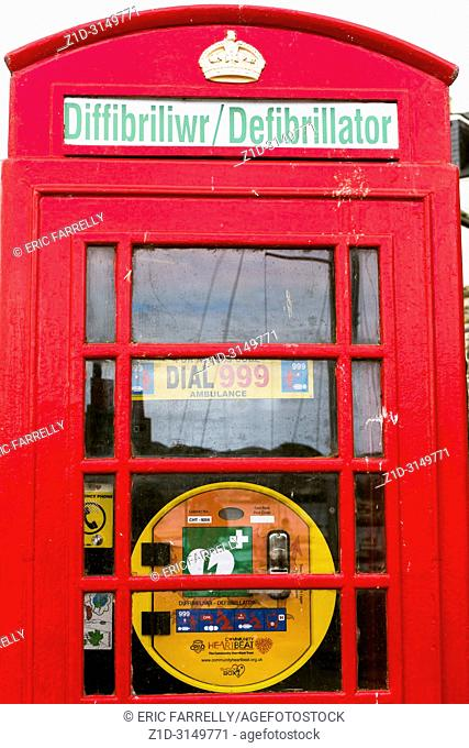 red telephone box converted to house emergency defibrillator in case of heart attacks , Conwy North Wales village UK