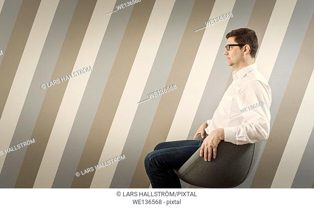 Portrait of pensive man sitting and waiting on chair in corridor