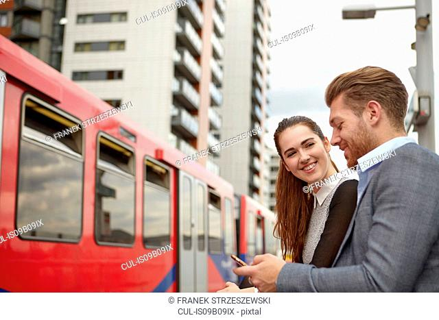 Businessman and woman reading smartphone texts on railway platform, London, UK