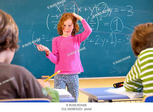 Primary schoolgirl scratching her head at equation on classroom blackboard