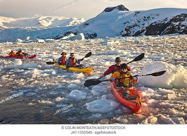 Kayakers paddle in brash ice among icebergs, Cierva Cove, Antarctic Peninsula