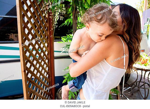 Boy kissing mother on shoulder