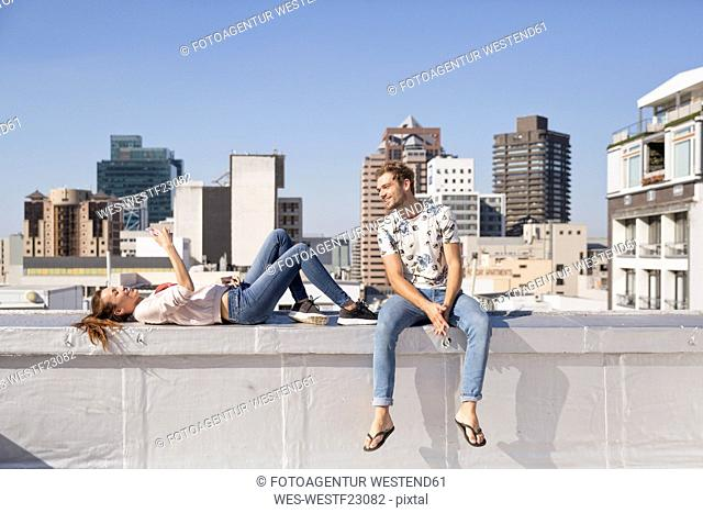 Young couple sitting on balustrade of a rooftop terrace, using smartphone