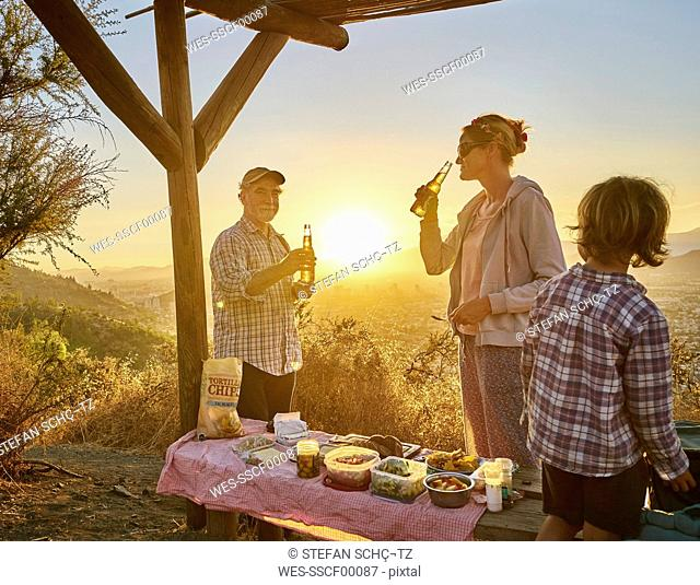 Chile, Santiago, mother with grandfather and son having a picnic in the mountains at sunset