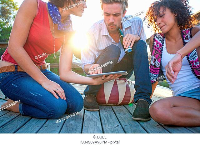 Young women and man using digital tablet on decking