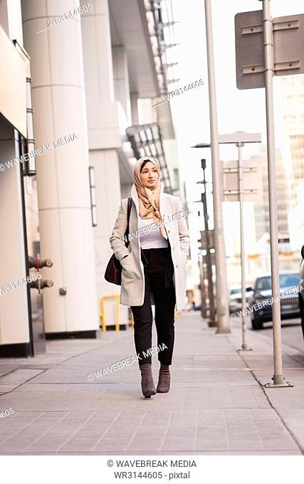 Woman in hijab walking on city street