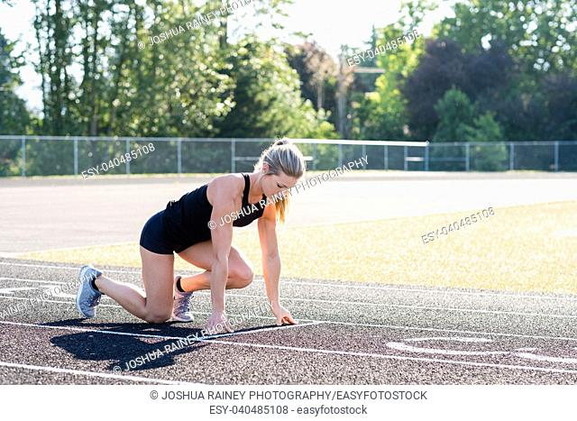 Young female runner in starting position for an outdoor track race in the summer