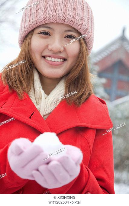 Woman Holding snowball outside in park