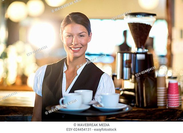 Portrait of waitress holding a tray with coffee cups
