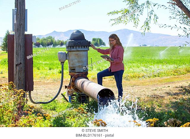 Caucasian farmer checking water pump