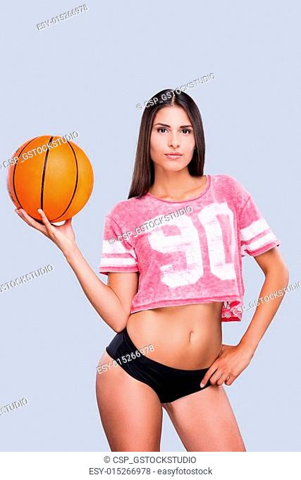 Ready to play? Attractive young female cheerleader holding basketball ball and looking at camera while standing against grey background