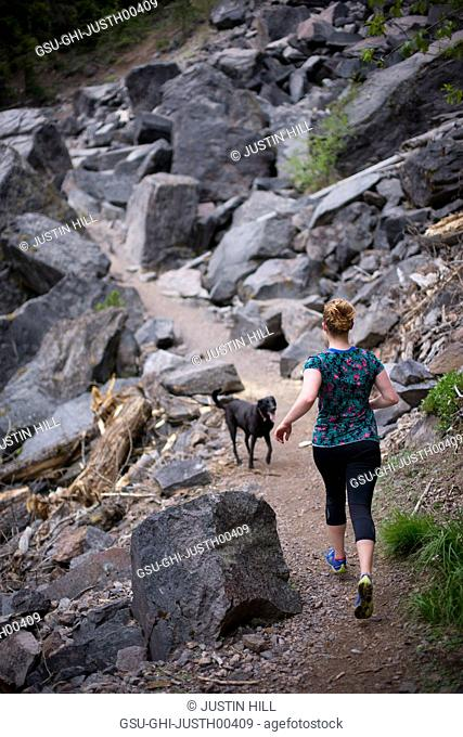 Young Woman Jogging with Dog on Rocky Trail