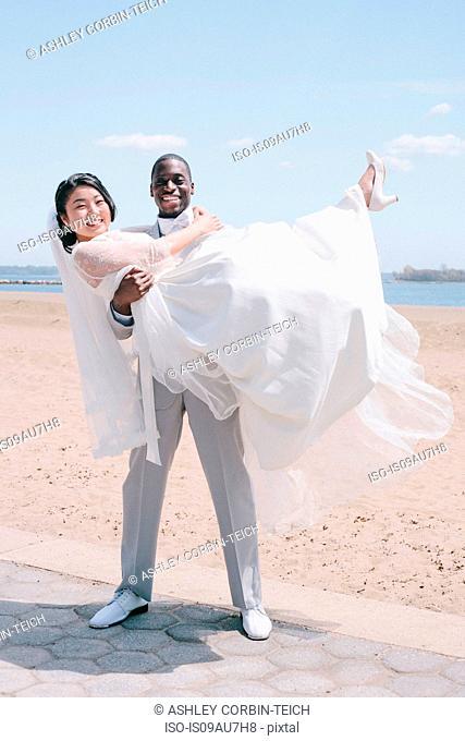 Bridegroom on beach carrying bride looking at camera smiling