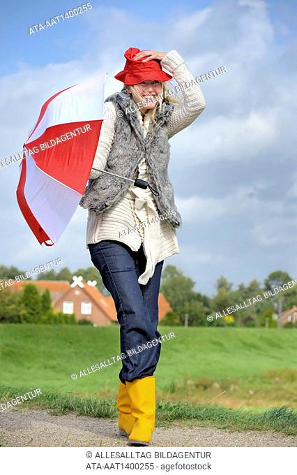Woman walking with an umbrella against strong wind