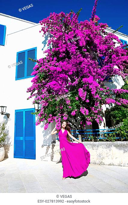 Beautiful young Woman in blowing dress before purple bougainvillea tree and famous white village with blue windows. Summer vacation