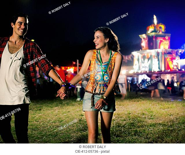 Couple holding hands and leaving music festival