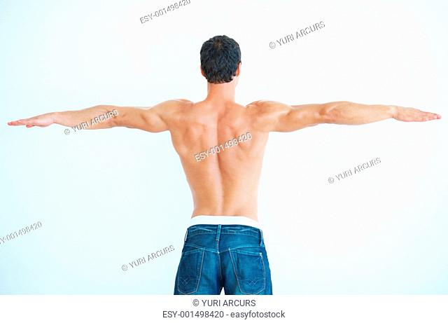 Rear view of muscular shirtless man with arms outstretched over white background