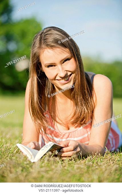 Brunette pretty woman in park reading a book and smiling at camera