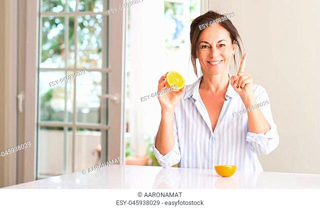 Middle aged woman holding orange fruit surprised with an idea or question pointing finger with happy face, number one