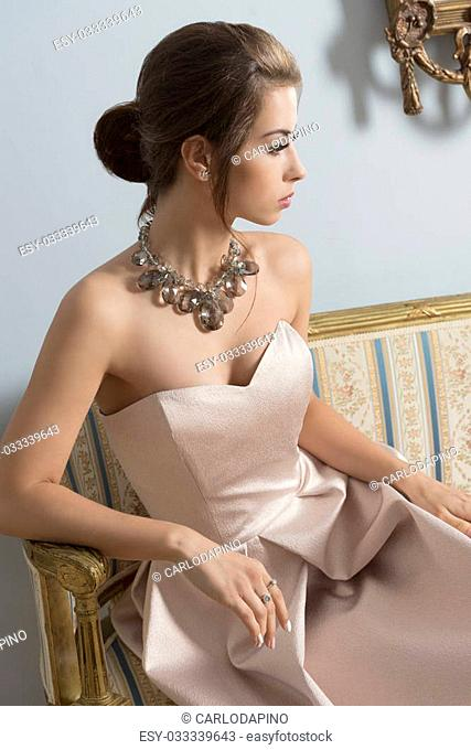 indoor portrait of aristocratic brunette girl sitting on vintage sofa with elegant pink dress, shiny necklace and classic hair-style