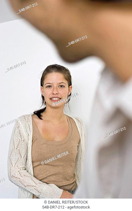 Smiling woman with man in foreground, Munich, Bavaria, Germany