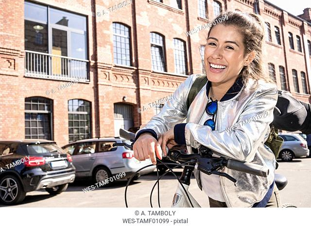 Portrait of laughing young woman leaning on bicycle handlebar
